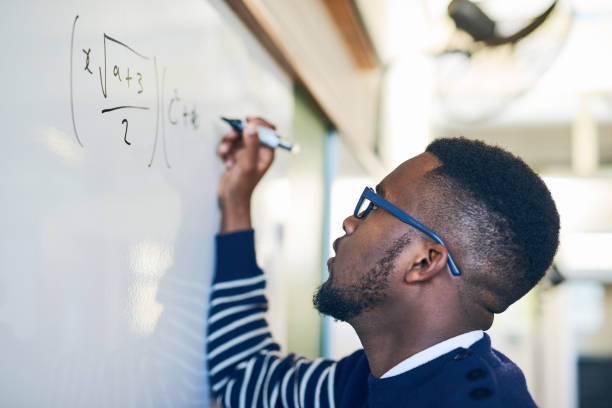 Just try until you get it right Cropped shot of a young man writing on a whiteboard in a classroom mathematical symbol stock pictures, royalty-free photos & images