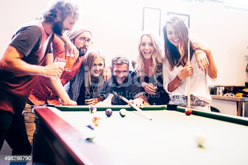 Hipster friends playing pool game indoors in a bar. They are also drinking, smiling and having fun.