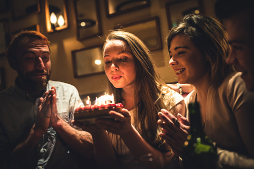 Friends celebrating birthday in a restaurant. Woman is holding a cake and blowing the candles. They are all smiling and having fun.