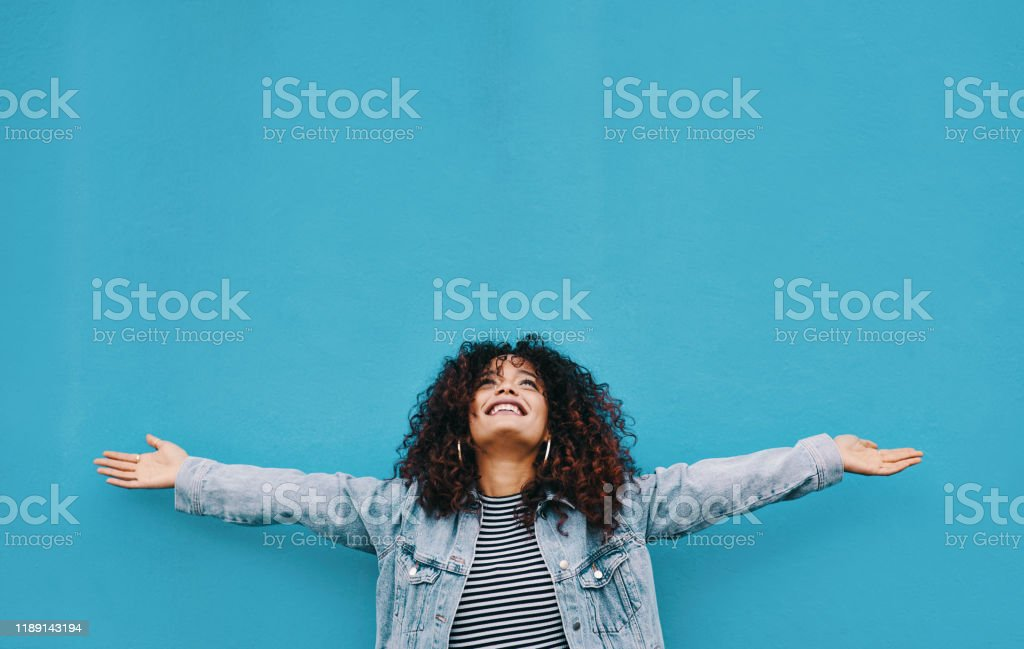 I just wanna celebrate life Cropped shot of an attractive young woman standing with her arms outstretched against a blue background 20-29 Years Stock Photo