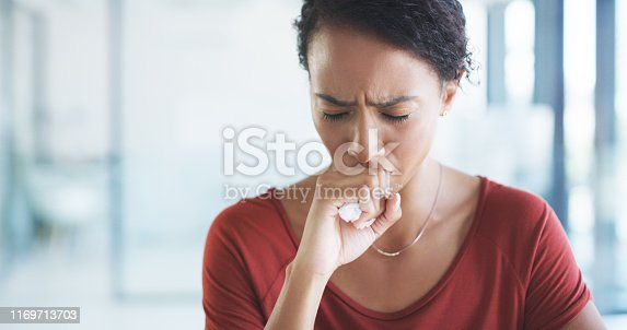 Cropped shot of an attractive young businesswoman sitting alone in her office and coughing as she suffers from a cold
