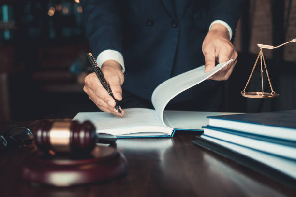justice and law concept. gavel on sounding block in hand's male judge at a courtroom, working with document law books, report the case on table in modern office. - lawyer stock pictures, royalty-free photos & images