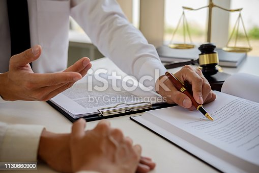istock Justice and Law concept. Legal counsel presents to the client a signed contract with gavel and legal law or legal having team meeting at law firm in background 1130660900