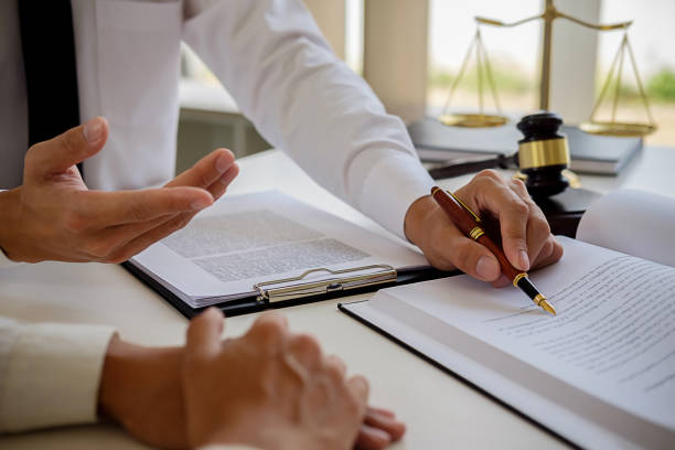 Justice and Law concept. Legal counsel presents to the client a signed contract with gavel and legal law or legal having team meeting at law firm in background stock photo