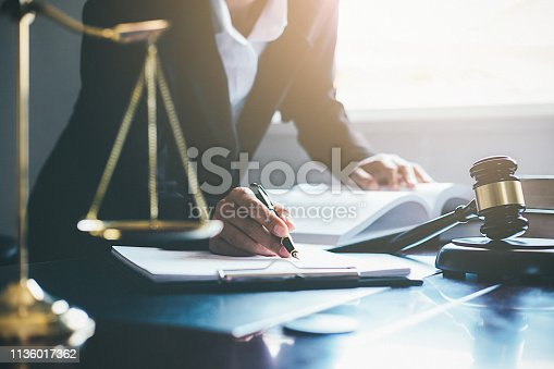 istock Justice and Law concept. Legal counsel presents to the client a signed contract with gavel and legal law or legal having team meeting at law firm in background 1136017362