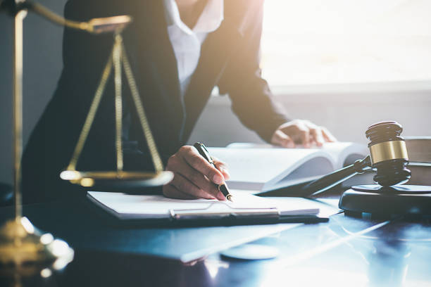 Justice and Law concept. Legal counsel presents to the client a signed contract with gavel and legal law or legal having team meeting at law firm in background Justice and Law concept. Legal counsel presents to the client a signed contract with gavel and legal law or legal having team meeting at law firm in background criminal stock pictures, royalty-free photos & images