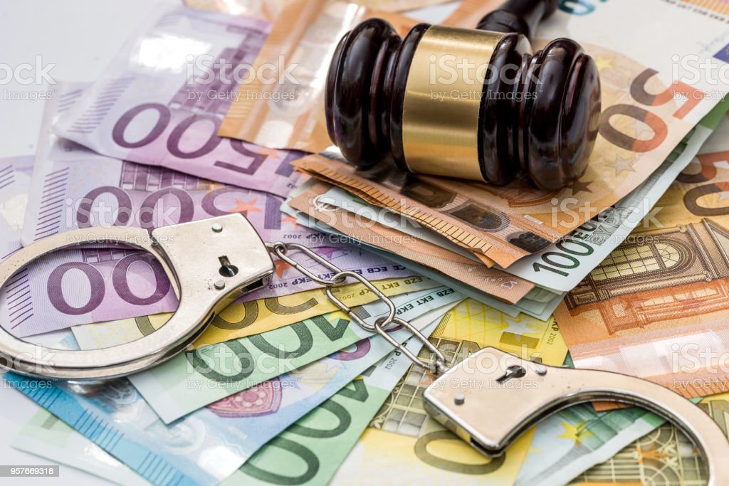 Justice, bribery and punishment. Euro with handcuffs and gavel stock photo