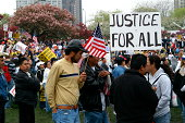 Chicago, Illinois, USA - May 01, 2006: A group of protestors gather to protest against immigration reform. A person in the crowd is holding a sign that reads and justice for all. The day was named May Day by protestors.