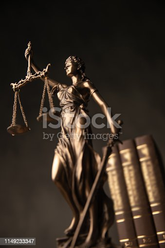 justice goddess statue with law books in the back, against grey studio background