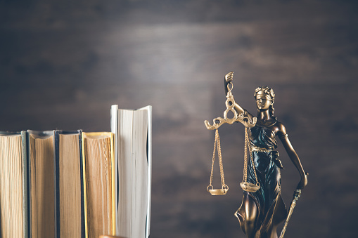 istock justice lady  and books on the dark background 1185464164