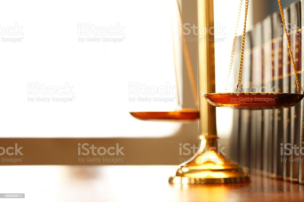 Justice Scale Next To Row Of Law Books A justice scale on a desk next to a row of law books. Light filters in through a window in the background creating ample negative space for coy.  Photographed using a very shallow depth of field. 2015 Stock Photo