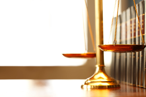 Justice Scale Next To Row Of Law Books Stock Photo - Download Image Now