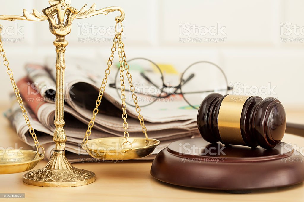 Justice scale with gavel, newspaper and eyeglasses stock photo
