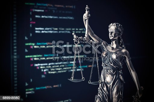 488389267istockphoto Justice statue with code on monitor device in background 689948580