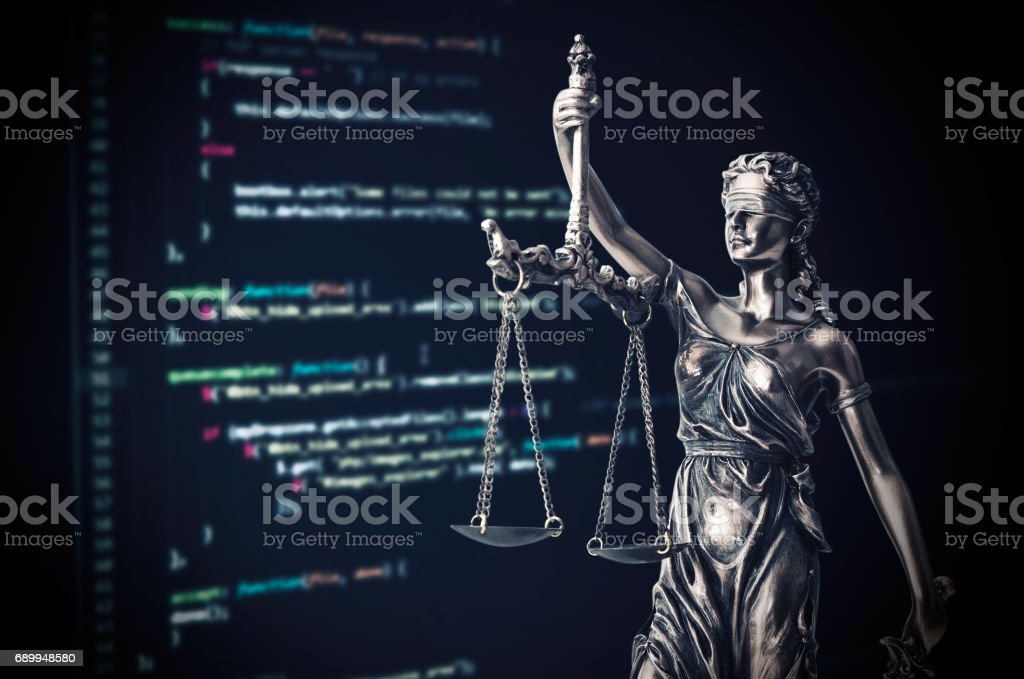 Justice statue with code on monitor device in background stock photo