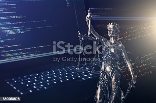 istock Justice statue with code on monitor device in background 689950828