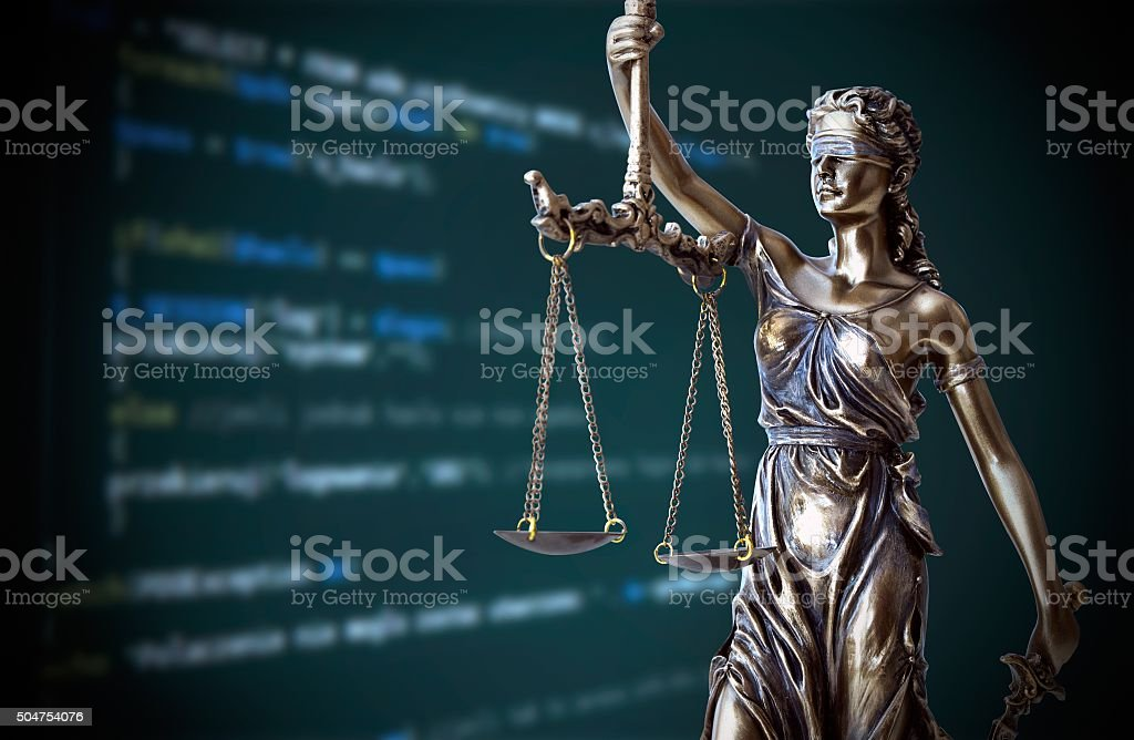 Justice statue with code on screen in background stock photo