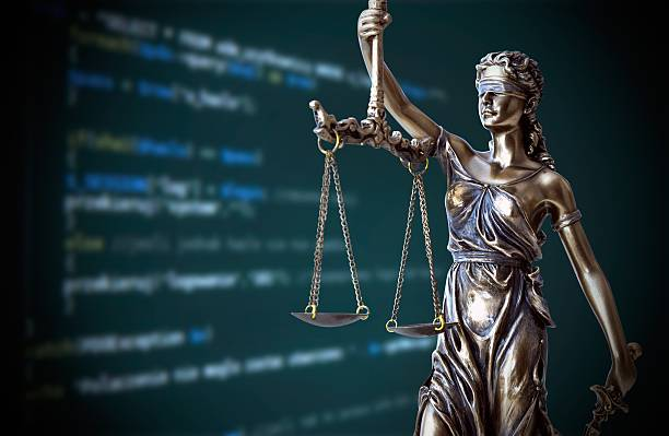 justice statue with code on screen in background - stealing crime stock photos and pictures