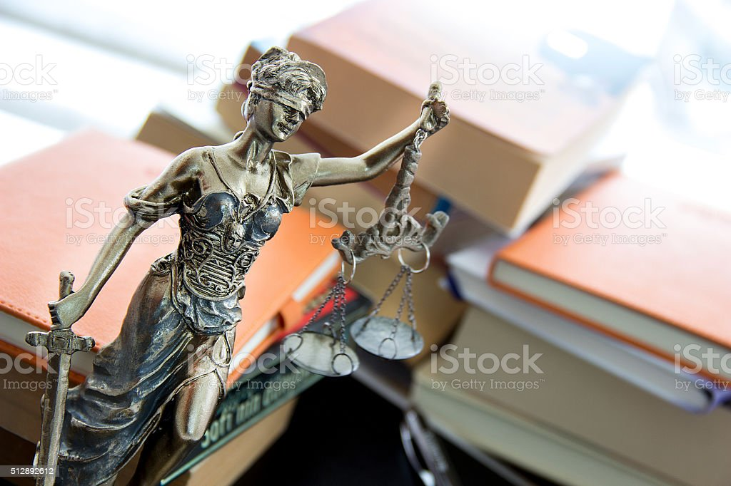 Justice statue with sword and scale and books. Law concept stock photo