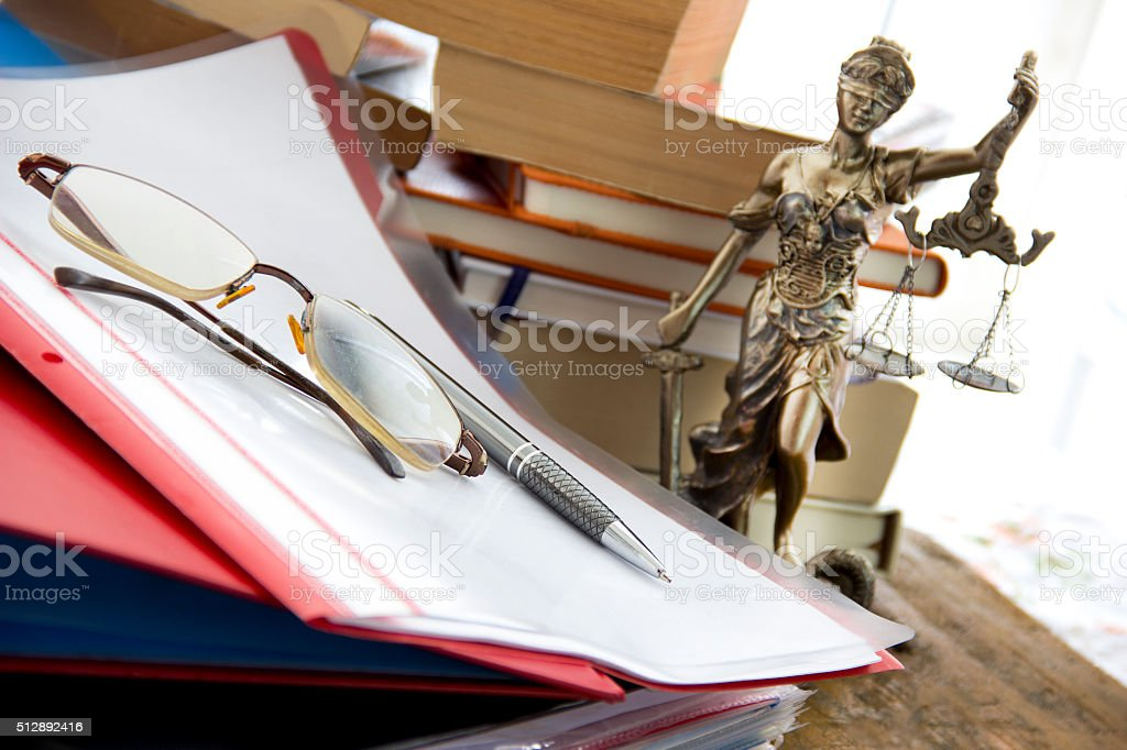 Justice statue with sword and scale, folders and books stock photo