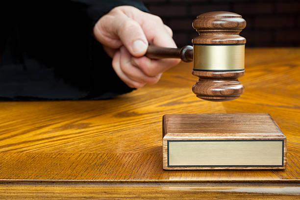 justice's hand pounds gavel to block with blank plaque - exploitatie stockfoto's en -beelden
