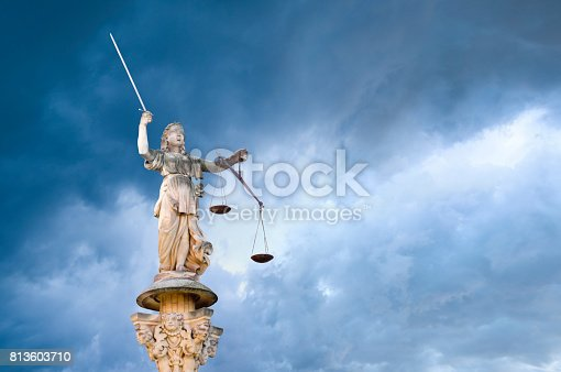 Justitia - Roman goddess of Justice in front of a dramatic sky