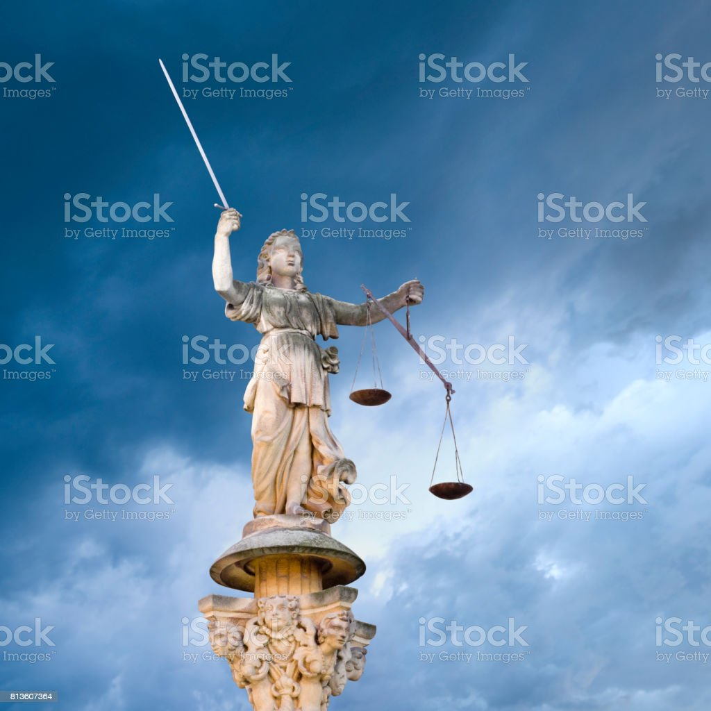 Justitia - Roman goddess of Justice in front of a dramatic sky stock photo