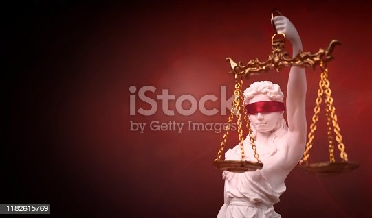 istock Justitia, the Roman goddess of Justice with red blindfold. Panoramic image with copy space. 1182615769