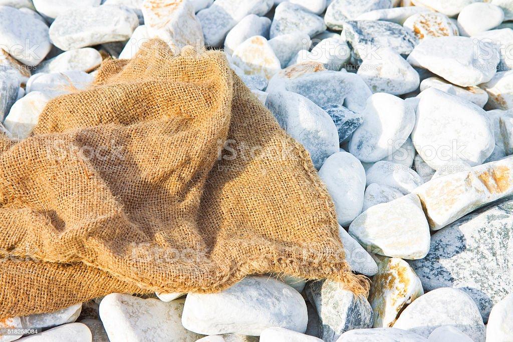 Jute bag left on a white gravel beach stock photo