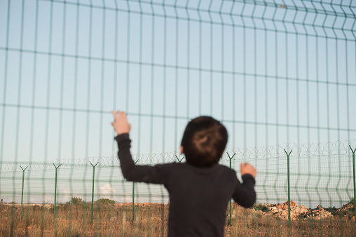 juvenile delinquent little refugee kid in displaced persons camp with high fence with barbed razor wire with hope of freedom