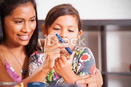A photograph of a mother helping her diabetic child monitor her blood sugar. Diabetes mellitus type 1, Juvenile diabetes.