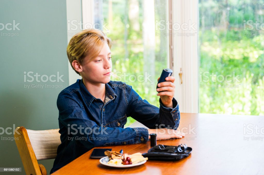 Juvenile diabetes patient checking his blood glucose levels at home stock photo