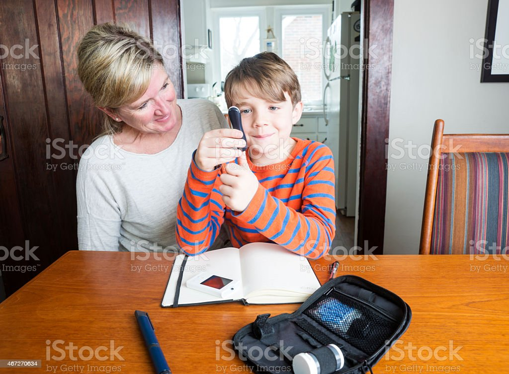 Juvenile diabetes patient with his mother at home stock photo