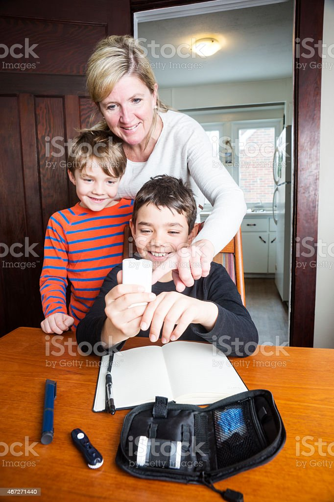 Juvenile diabetic boy with his family monitoring blood sugar stock photo