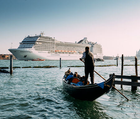 Juxtaposition of gondola and huge cruise ship in Giudecca Canal. Old and new transportation on the Venice Lagoon