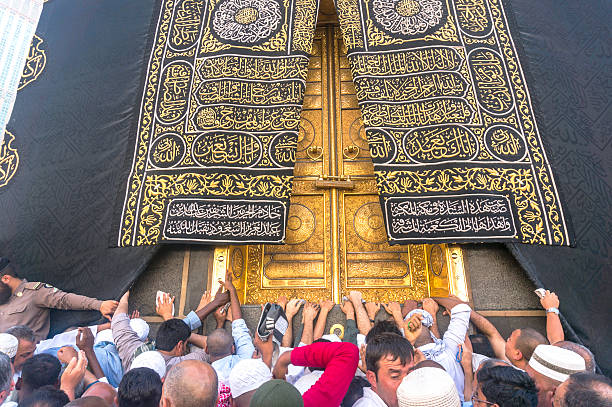 Kaaba Mecca, Saudi Arabia - March 14, 2015: A close up view of kaaba door and the kiswah (cloth that covers the kaaba) at Masjidil Haram in Makkah, Saudi Arabia. The door is made of pure gold. circumambulation stock pictures, royalty-free photos & images