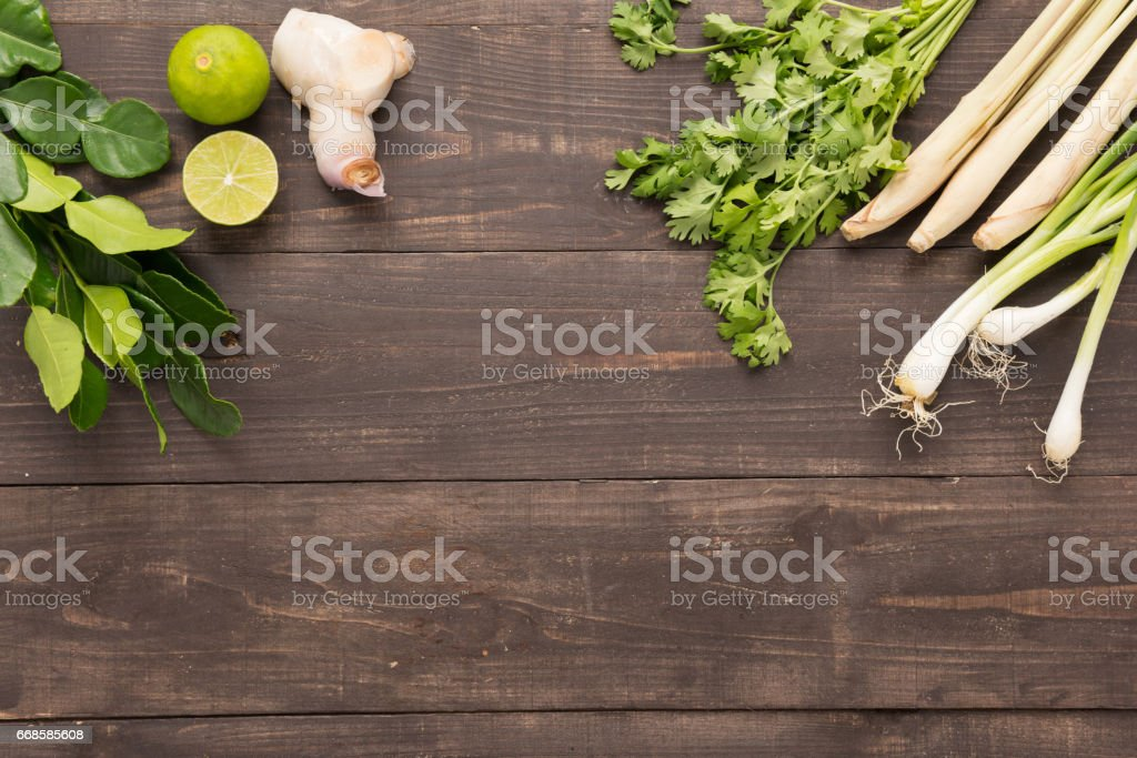 Kaffir lime leaves, coriander or cilantro, Ginger, lemon, lemon grass and green onions on wooden background. Overhead view stock photo
