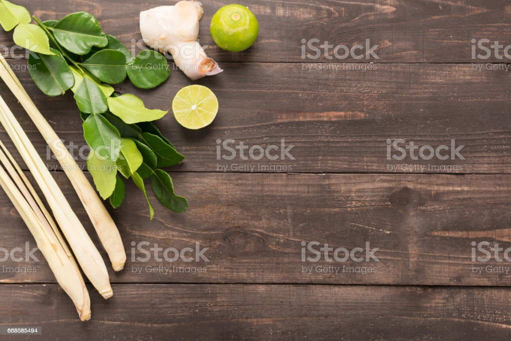 Kaffir lime leaves, Ginger, lemon and Green onions on wooden background. Overhead view stock photo