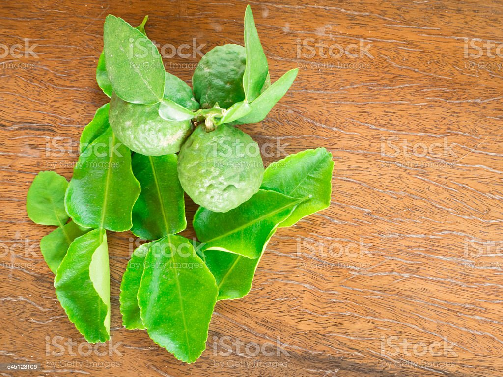 Kaffir lime leaves on wood paint background stock photo