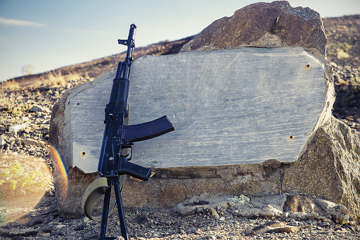 Kalashnikov assault rifle close-up on a background of granite slabs, hill and blue sky in the background