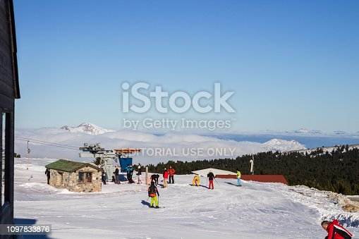 istock kalavrita, greece, 1/22/2019 ski resort top of a mountain with snowboarders and forest and clouds 1097833876
