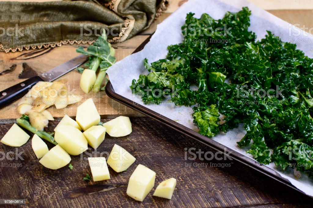 Kale and potatoes on rustic wood food preparation flat lay stock photo