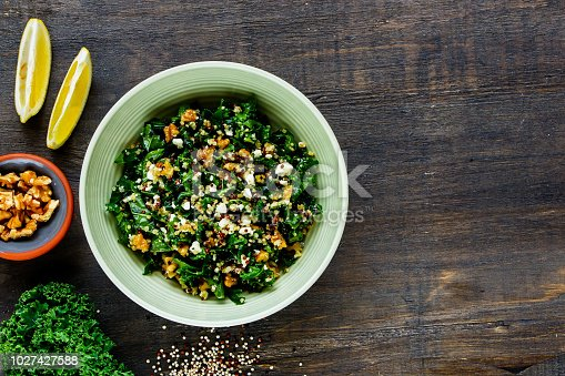 Close up of detox salad bowl. Healthy raw kale and quinoa salad with feta cheese and walnut on wooden background. Top view. Flat lay. Clean eating, dieting, vegetarian food concept