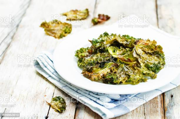 Kale chips Kale chips on wood background. toning. selective focus Appetizer Stock Photo