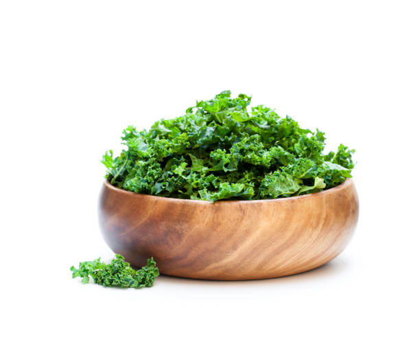 kale  leafs in wooden bowl isolated on white background stock photo