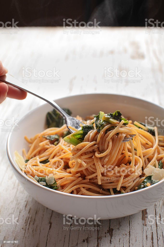 Kale Pasta Dish with hand stock photo