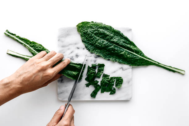 Kale Woman hands cutting organic green kale leaves on a marble board over a white table background, healthy cooking nutrition concept, top view kale stock pictures, royalty-free photos & images