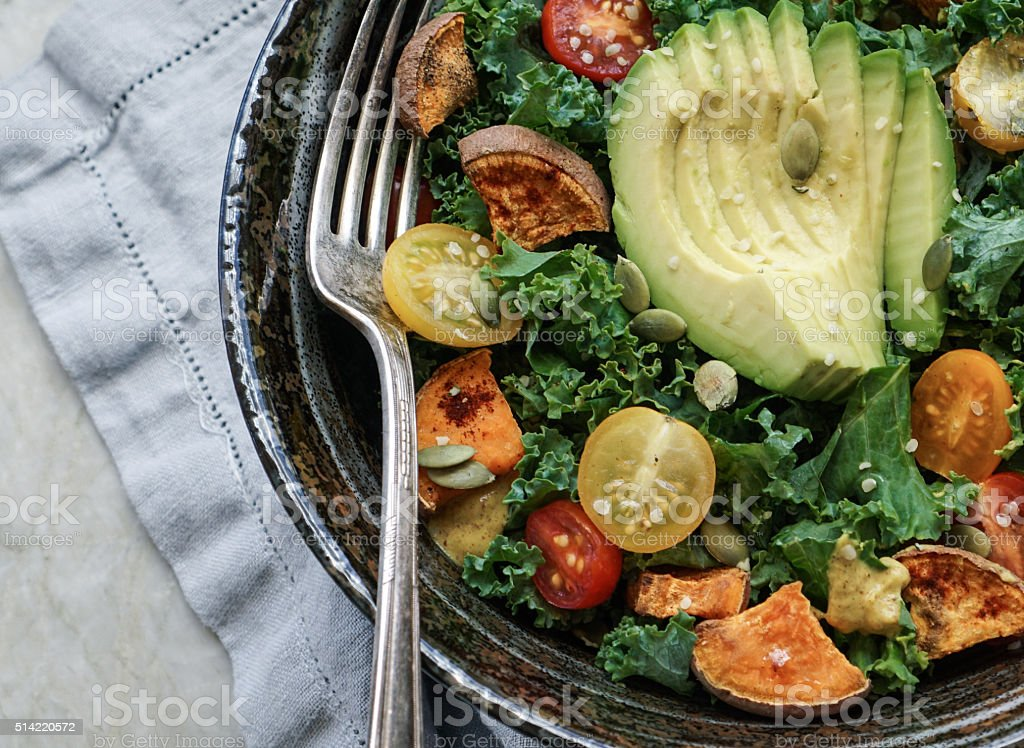 Kale, roasted yams and avocado salad stock photo