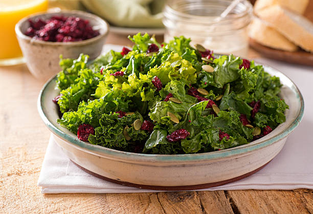 Kale Salad A delicious kale salad with dried cranberry and pumpkin seed. kale stock pictures, royalty-free photos & images