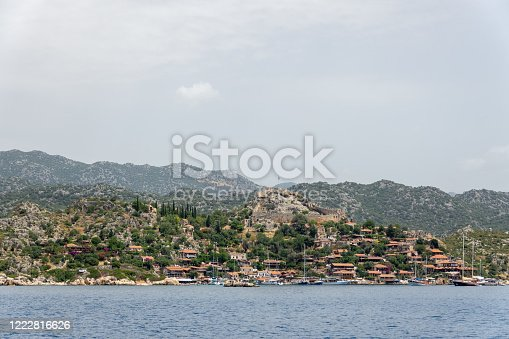 istock Kalekoy village with stone built houses and castle on top of hill in Uchagiz bay in Turkey 1222816626